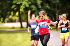 Young woman running in the crowd crossing the finish line. Royalty Free Stock Photography