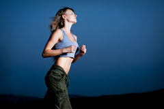 Young woman running in the dark Royalty Free Stock Photo