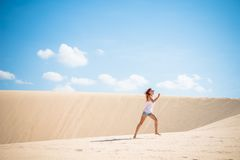 Young woman running on dunes Stock Photos