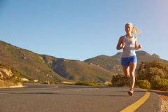 Young woman running on an empty road Stock Photo