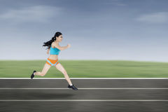 Young woman running on the field. Young athletic woman running on a track Stock Photos
