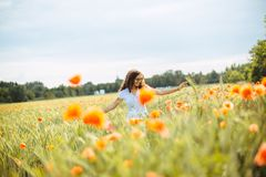 Young woman running through a field of wildflowers royalty free stock image