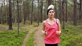 Woman running at forest trail and listening music from smart phone stock footage