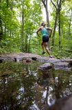 Young woman running forest trail past a stream with reflection in water. A young woman running forest trail past a stream with reflection in water Stock Image