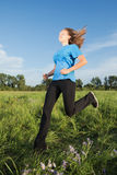 Young  woman running on the grass Stock Image