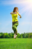 Young woman running on a green meadow Stock Photo
