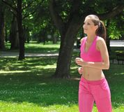 Young woman running in green park Royalty Free Stock Photo