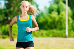 Young woman running in green park Royalty Free Stock Photography