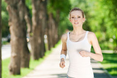 Young woman running in green park Stock Photos