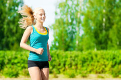 Young woman running in green park Stock Photography
