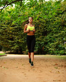 Young woman running in green park, fitness outdoor Royalty Free Stock Image
