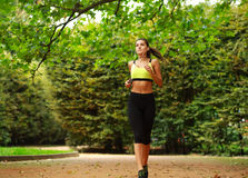 Young woman running in green park, fitness outdoor Stock Images