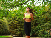 Young woman running in green park, fitness outdoor Royalty Free Stock Photo