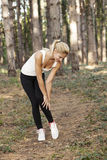 Young woman after running had injuries. In the park Stock Image
