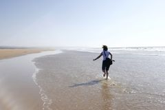 Young woman running happily on a beach royalty free stock images