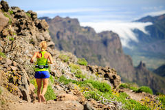 Young woman running or hiking in mountains Stock Image