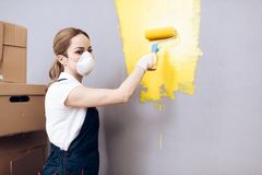 Young woman running a house painter. A woman is engaged in painting the walls. Royalty Free Stock Photo