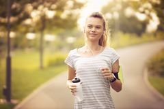 Free Young Woman Running In Park And Listening To Music With Headphones - Beautiful Blonde And Fit Girl Jogging Alone Outdoor In Early Royalty Free Stock Photos - 158448148