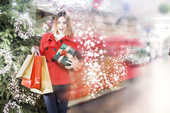Young woman is running inside a Christmas gifts shop Stock Photos