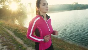 A young woman running  at lake at sunrise. stock footage