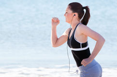 Young woman running and listening to music Royalty Free Stock Photo