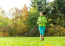 Young woman running and listening to music. Royalty Free Stock Photos