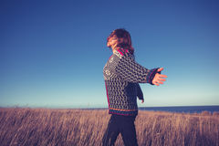 Young woman running through meadow by the sea Stock Photo