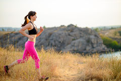 Young Woman Running on the Morning Trail. Active Lifestyle Concept. Stock Photo