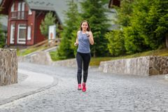 Young woman running in mountain european town in the morning royalty free stock photos