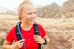 Young woman running in mountains on sunny day Stock Photo