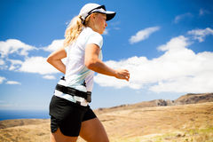 Young woman running in mountains on sunny summer d Stock Photo