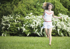 Young woman running on nature, smiling and looking at camera. Royalty Free Stock Photography