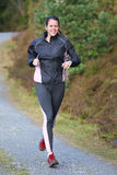 Young woman running outdoor. Smiling young woman running outdoor Royalty Free Stock Image