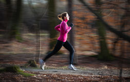 Young woman running outdoors in a city park Stock Images