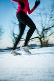 Young woman running outdoors on a cold winter day. (motion blurred image Royalty Free Stock Images