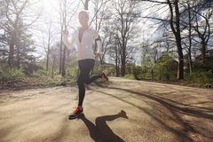 Young woman running outdoors in forest Stock Photos