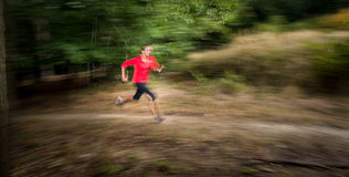Young woman running outdoors in a forest Stock Photo