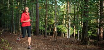 Young woman running outdoors in a forest stock images