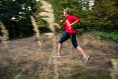 Young woman running outdoors in a forest. Going fast motion blurred image Stock Photo