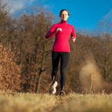 Young woman running outdoors on a lovely sunny day Royalty Free Stock Image