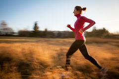 Young woman running outdoors on a lovely sunny day Royalty Free Stock Images