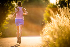 Young woman running outdoors on a lovely sunny summer evening Stock Photos