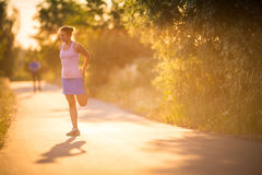 Young woman running outdoors on a lovely sunny summer evening Royalty Free Stock Photo