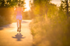 Young woman running outdoors on a lovely sunny summer evening Royalty Free Stock Photos