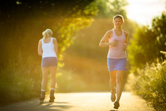 Young woman running outdoors on a lovely sunny summer evening Stock Image