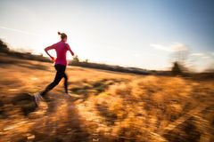 Young woman running outdoors. On a lovely sunny winter/fall day motion blurred image Stock Image