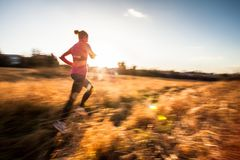Young woman running outdoors. On a lovely sunny winter/fall day motion blurred image Royalty Free Stock Photo
