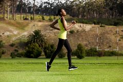 Young woman running outdoors in a park Royalty Free Stock Images