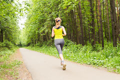 Young woman running outdoors in the park. Stock Photos