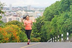 Young  woman running outdoors in park. With city scene background Stock Photos